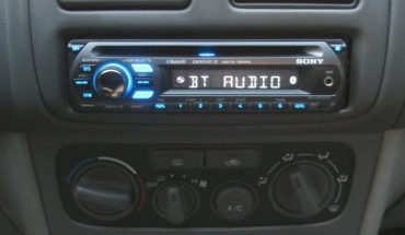 Car_dashboard_with_MEX-BT2500_head_unit_and_BCT-15_radio_scanner_installed_and_illuminated